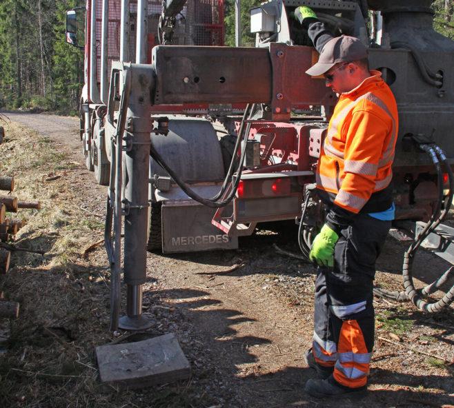 Kuljettaja laittaa tukijalan alle suojalevyn, jotta tien pinta ei vaurioidu.