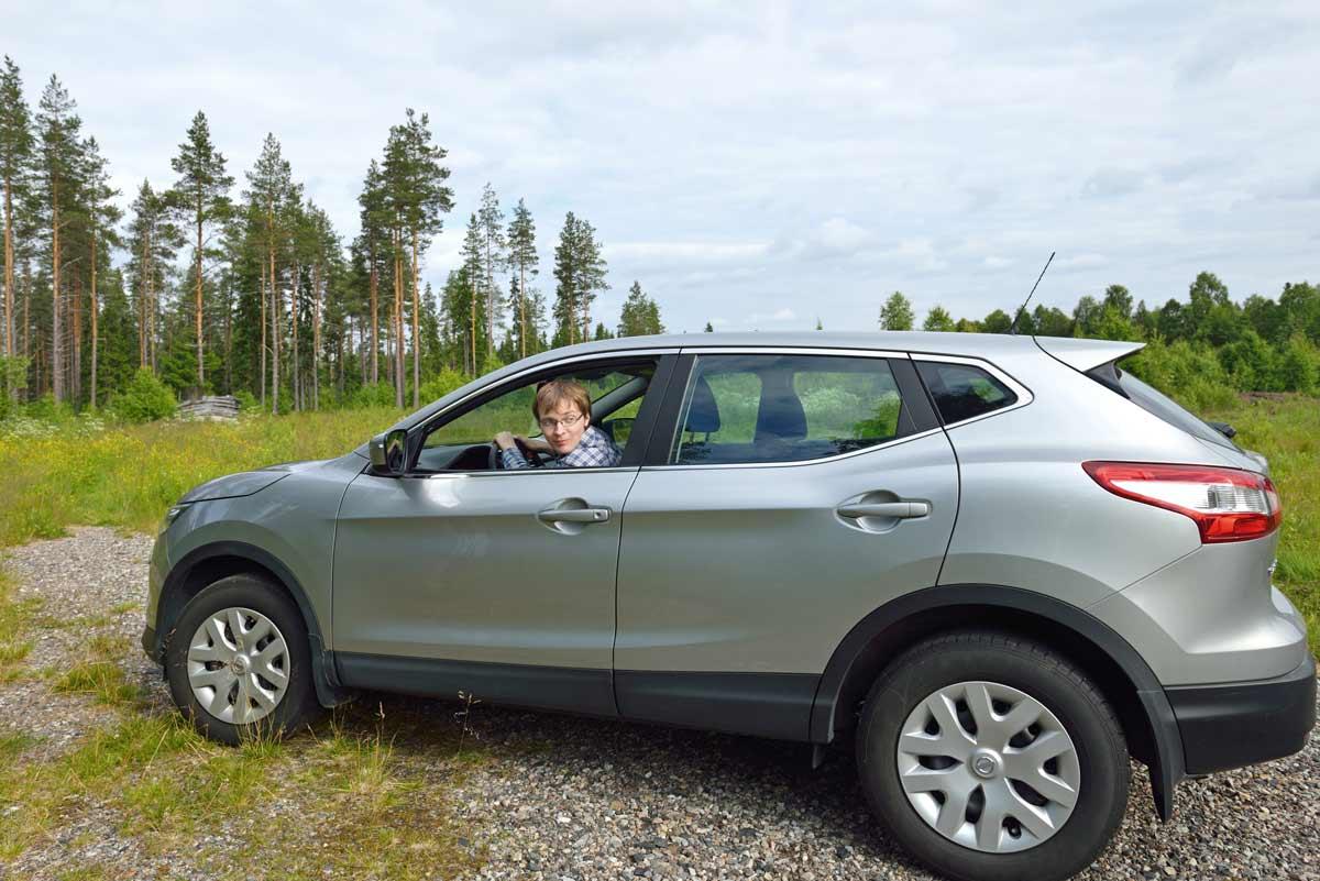 Henkilö yksin metsän keskellä autolla.