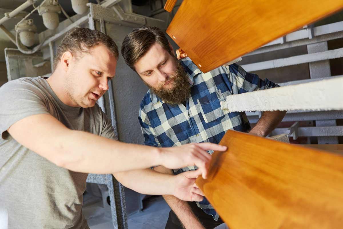 Kaksi miestä keskustelevat työpaikalla puisen esineen työstämisestä.