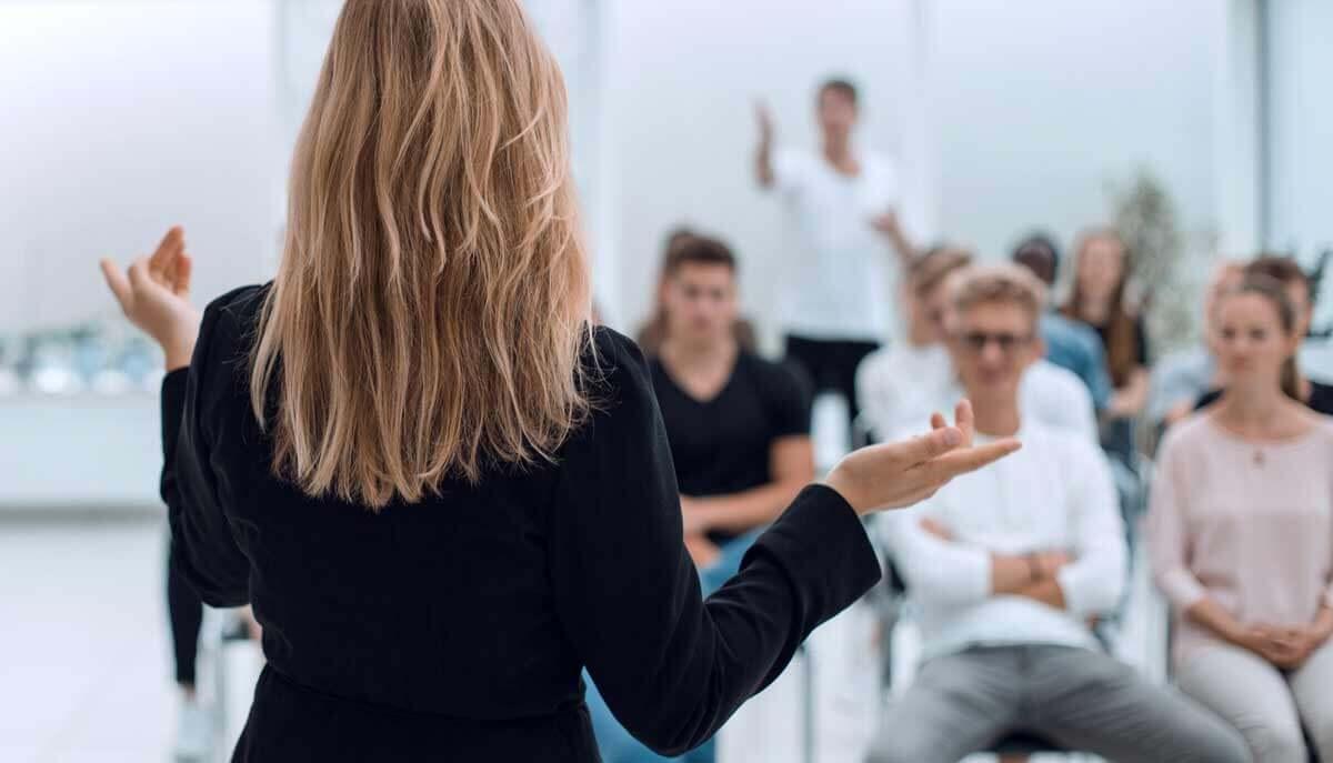Nainen pitää esitystä ryhmälle.