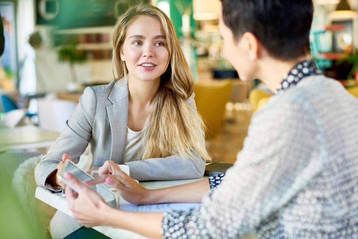 Kaksi henkilöä keskustelee pöydän äärellä.