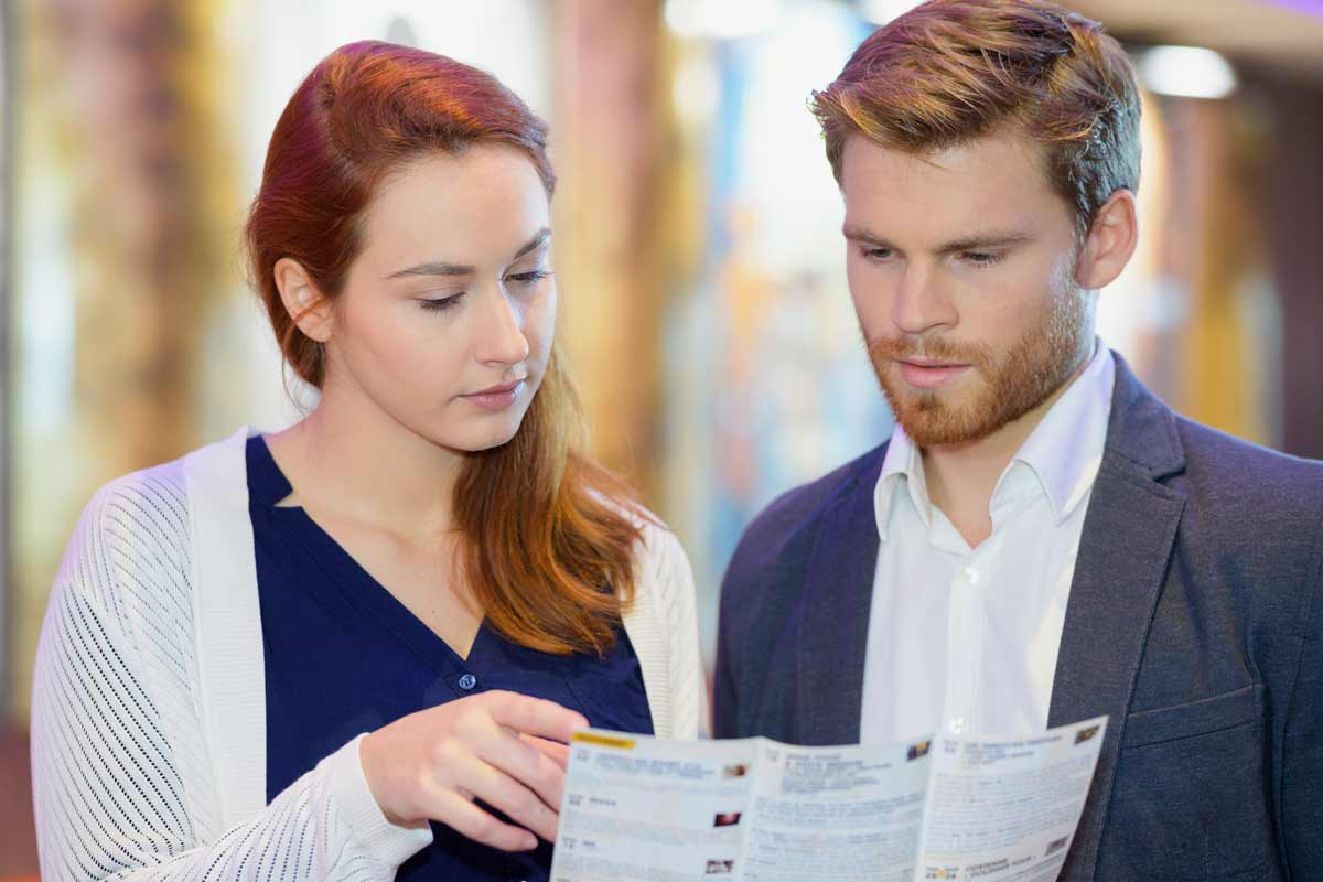 Kaksi nuorta työntekijää keskustelemassa esitteestä.