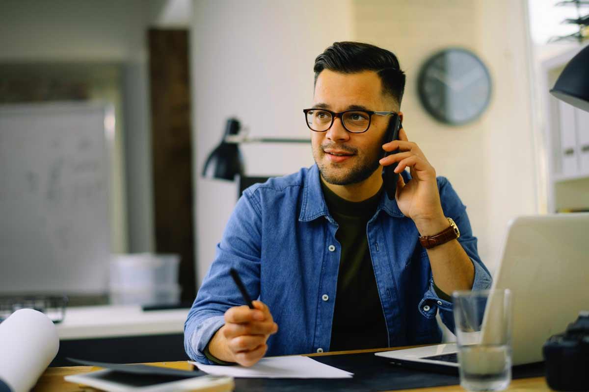 Mies puhuu puhelimessa työpaikallaan.