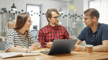 Kolme työntekijää keskustelmassa pöydän ympärillä.