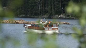 veneilijöitä liikkeellä puutavaralautan läheisyydessä